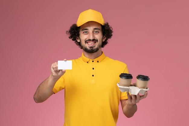 Widok Z Przodu Męski Kurier W żółtym Mundurze I Pelerynie Trzymający Brązowe Filiżanki Z Kawą I Kartkę Na Różowej ścianie Darmowe Zdjęcia
