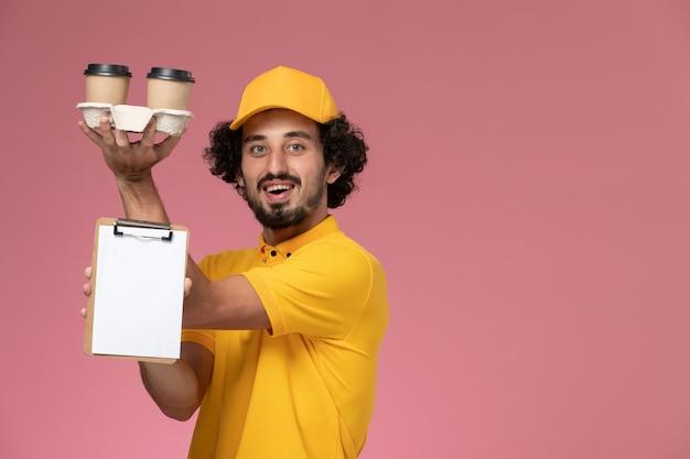 Widok Z Przodu Męski Kurier W żółtym Mundurze I Pelerynie Trzymający Brązowe Filiżanki Z Kawą I Notatnik Na Jasnoróżowej ścianie Darmowe Zdjęcia