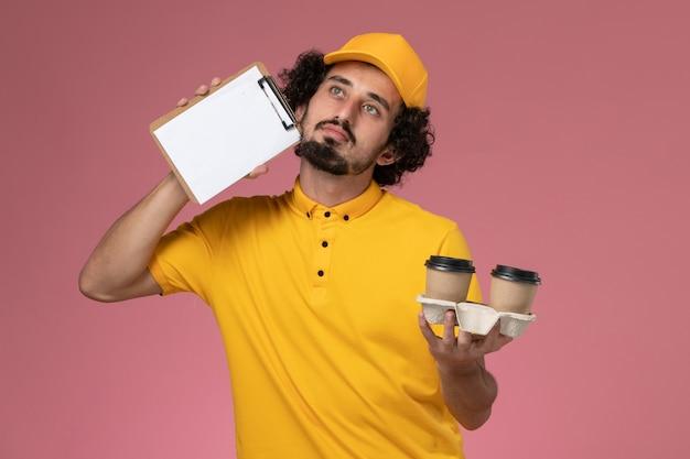 Widok Z Przodu Męski Kurier W żółtym Mundurze I Pelerynie Trzymający Brązowe Filiżanki Z Kawą I Notatnik Na Różowej ścianie Darmowe Zdjęcia
