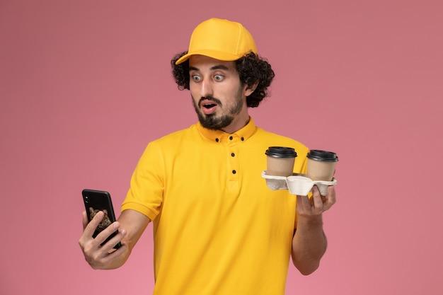 Widok Z Przodu Męski Kurier W żółtym Mundurze I Pelerynie Trzymający Brązowe Filiżanki Z Kawą I Telefon Na Różowej ścianie Darmowe Zdjęcia