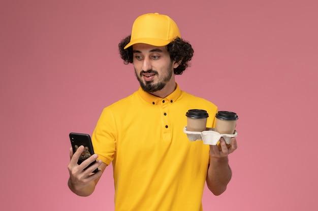 Widok Z Przodu Męski Kurier W żółtym Mundurze I Pelerynie, Trzymający Brązowe Filiżanki Z Kawą I Używający Telefonu Na Różowej ścianie Darmowe Zdjęcia
