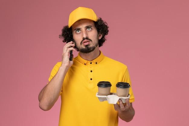 Widok Z Przodu Męski Kurier W żółtym Mundurze I Pelerynie Trzymający Brązowe Kubki Dostawy Kawy Rozmawiający Przez Telefon Na Różowej ścianie Darmowe Zdjęcia