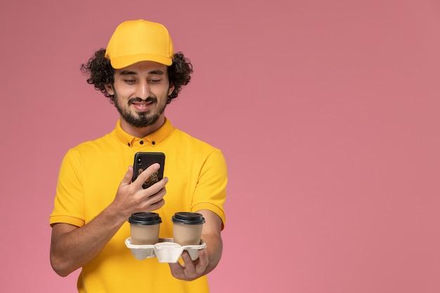 Widok Z Przodu Męski Kurier W żółtym Mundurze I Pelerynie Trzymający Brązowe Kubki Z Kawą I Robiąc Im Zdjęcie Na Różowej ścianie Darmowe Zdjęcia