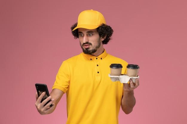 Widok Z Przodu Męski Kurier W żółtym Mundurze I Pelerynie Trzymający Brązowe Kubki Z Kawą I Telefon Na Różowej ścianie Darmowe Zdjęcia