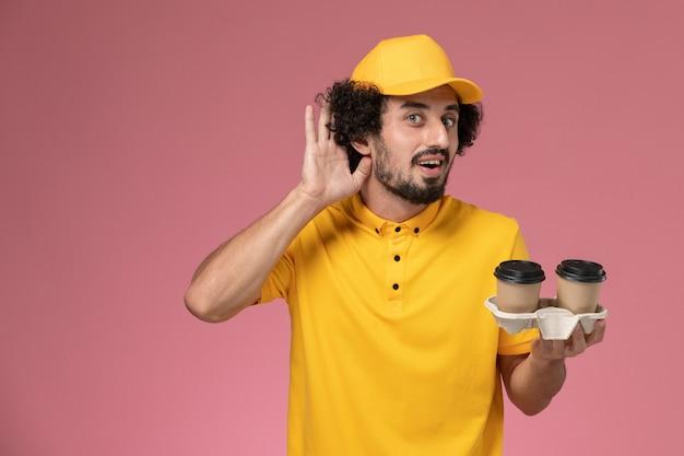 Widok Z Przodu Męski Kurier W żółtym Mundurze I Pelerynie Trzymający Brązowe Kubki Z Kawą, Próbujący Usłyszeć Na Różowej ścianie Darmowe Zdjęcia