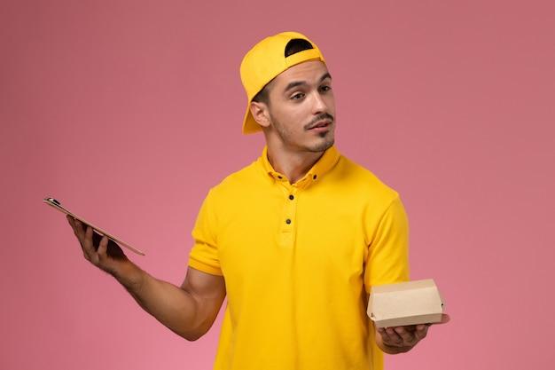 Widok Z Przodu Męski Kurier W żółtym Mundurze I Pelerynie, Trzymający Małą Paczkę Z Jedzeniem I Notatnik Na Jasnoróżowym Tle. Darmowe Zdjęcia