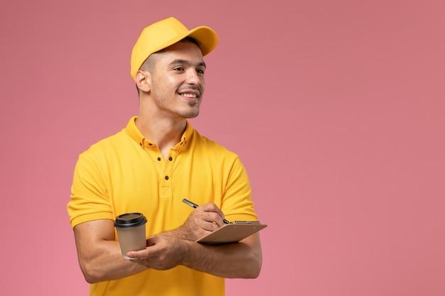 Widok Z Przodu Męski Kurier W żółtym Mundurze, Trzymając Dostarczającą Filiżankę Kawy I Notatnik Zapisujący Notatki Na Różowym Biurku Darmowe Zdjęcia