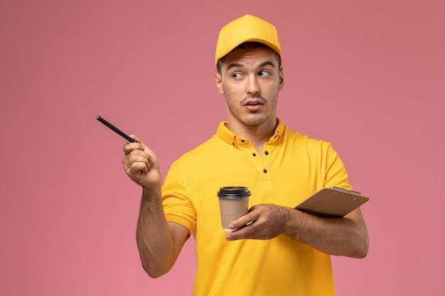 Widok Z Przodu Męski Kurier W żółtym Mundurze Trzymający Dostawczą Filiżankę Kawy I Notatnik Zapisujący Notatki Na Jasnoróżowym Biurku Darmowe Zdjęcia