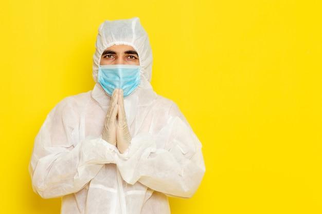 Widok Z Przodu Męskiego Pracownika Naukowego W Specjalnym Białym Kombinezonie Ochronnym Iz Maską Pozującą Na żółtej ścianie Darmowe Zdjęcia