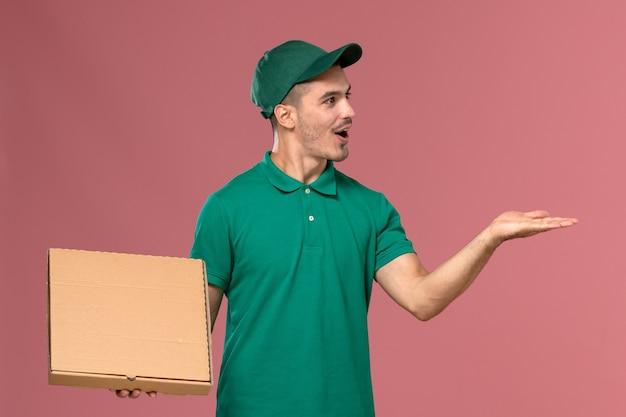 Widok Z Przodu Mężczyzna Kurier W Zielonym Mundurze, Trzymając Pudełko Na żywność Na Różowym Tle Darmowe Zdjęcia