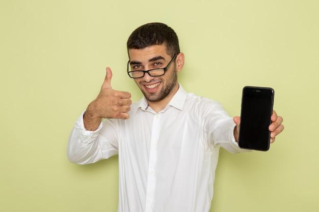 Widok Z Przodu Mężczyzna Pracownik Biurowy W Białej Koszuli, Trzymając Smartfon Na Zielonej ścianie Darmowe Zdjęcia