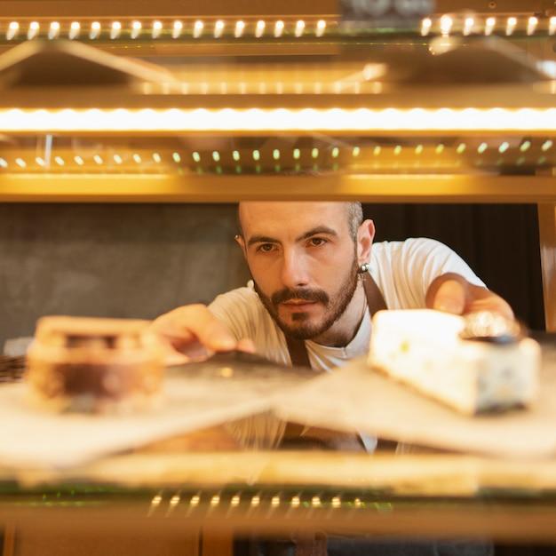 Widok z przodu mężczyzna sprawdzanie produktów kawiarni Darmowe Zdjęcia
