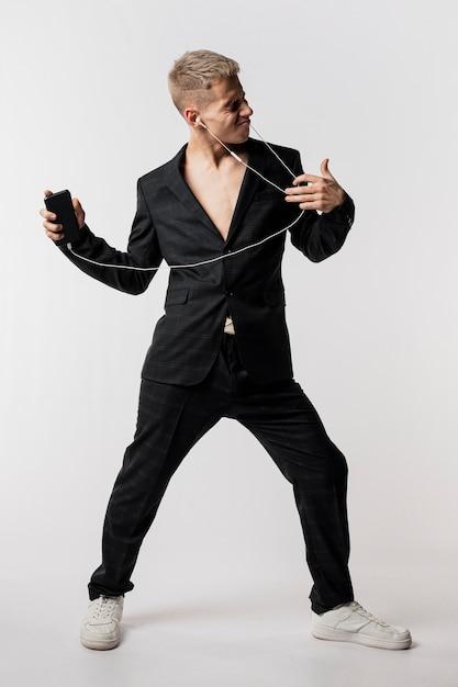 Widok Z Przodu Mężczyzna Tancerz W Garniturze Słuchania Muzyki Na Słuchawkach Darmowe Zdjęcia