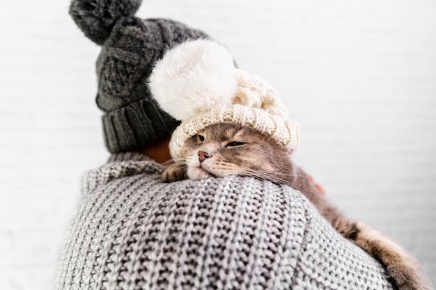 Widok z przodu mężczyzny i kota w futrzanej czapce Darmowe Zdjęcia
