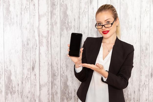 Widok Z Przodu Młoda Bizneswoman W ścisłej Czarnej Kurtce Trzymając Telefon Na Białym Biurku Darmowe Zdjęcia
