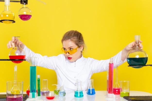 Widok Z Przodu Młoda Chemiczka W Białym Garniturze Przed Stołem Z Roztworami Ed Pracującymi Z Nimi Mieszającymi Się Na żółtej Kosmicznej Chemii Darmowe Zdjęcia