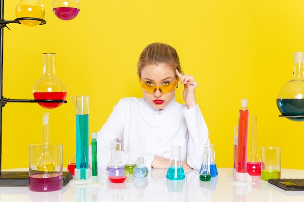 Widok Z Przodu Młoda Chemiczka W Białym Garniturze Przed Stołem Z Rozwiązaniami Ed Pracującymi Z Nimi Mieszającymi Się Na żółtej Kosmicznej Pracy Naukowej Z Chemii Darmowe Zdjęcia