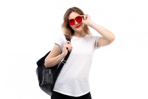 Widok Z Przodu Młoda Dama W Białej Koszulce Czerwone Okulary Przeciwsłoneczne Czarna Torba Uśmiechnięta Na Białym Darmowe Zdjęcia