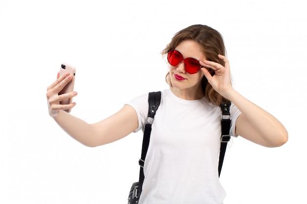 Widok Z Przodu Młoda Dama W Białej Koszuli Czerwonych Okularów Przeciwsłonecznych Czarnej Torbie Uśmiecha Się Przy Selfie Na Białym Darmowe Zdjęcia