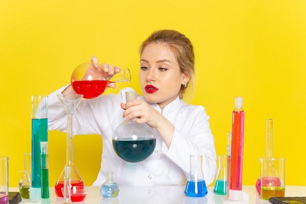 Widok Z Przodu Młoda Kobieta Chemik W Białym Garniturze, Trzymając Różne Roztwory Mieszając Na żółtej Przestrzeni Chemii Pracy Darmowe Zdjęcia