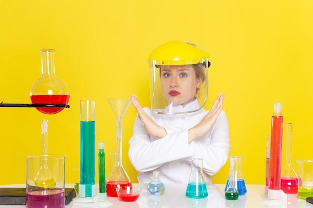 Widok Z Przodu Młoda Kobieta Chemik W Białym Garniturze Z Roztworami Ed Pracującymi Z Nimi W Hełmie Na żółtym Procesie Chemii Kosmicznej Darmowe Zdjęcia
