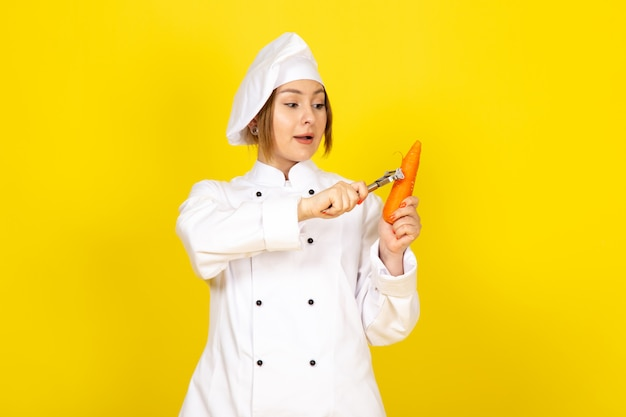 Widok Z Przodu Młoda Kobieta Kucharz W Białym Garniturze I Białej Czapce Trzyma I Czyści Pomarańczową Marchewkę Na żółto Darmowe Zdjęcia