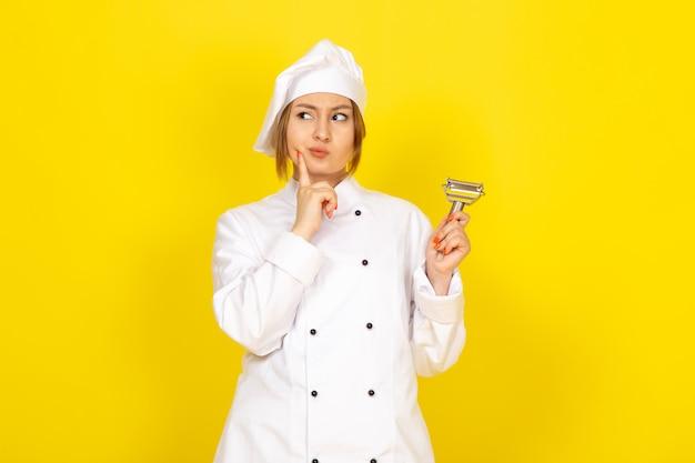 Widok Z Przodu Młoda Kobieta Kucharz W Białym Garniturze I Białej Czapce Trzyma środek Czyszczący Do Warzyw Stwarzających Myślenie Na żółto Darmowe Zdjęcia