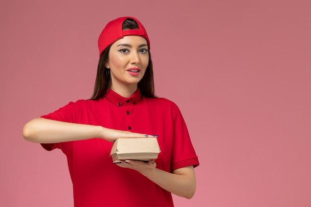 Widok Z Przodu Młoda Kobieta Kurier W Czerwonym Mundurze I Pelerynie Z Małym Pakietem żywności Dostawy Na Rękach Na Różowej ścianie Darmowe Zdjęcia
