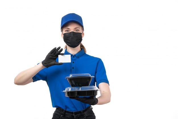 Widok Z Przodu Młoda Kobieta Kurier W Niebieskie Jednolite Czarne Rękawiczki I Czarną Maskę Trzyma Miski Dostawy żywności I Białą Kartę Darmowe Zdjęcia
