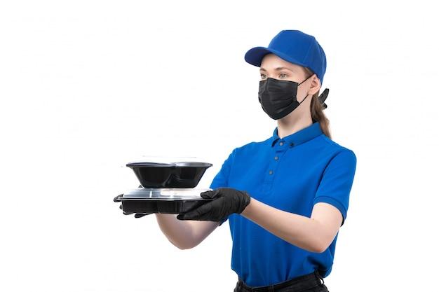 Widok Z Przodu Młoda Kobieta Kurier W Niebieskie Jednolite Czarne Rękawiczki I Czarną Maskę Trzyma Miski Dostawy żywności Darmowe Zdjęcia