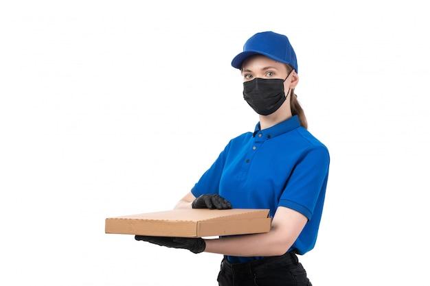 Widok Z Przodu Młoda Kobieta Kurier W Niebieskie Jednolite Czarne Rękawiczki I Czarną Maskę Trzyma Pakiet Dostawy żywności Darmowe Zdjęcia