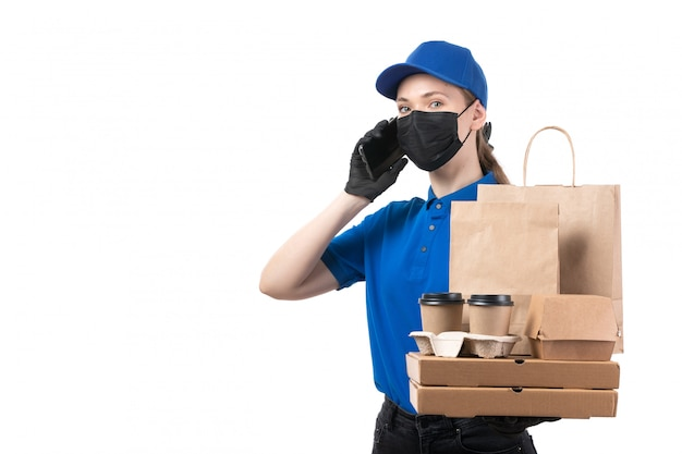 Widok Z Przodu Młoda Kobieta Kurier W Niebieskie Jednolite Czarne Rękawiczki I Czarną Maskę Trzymająca Paczki Z Dostawą żywności I Smartfon Darmowe Zdjęcia