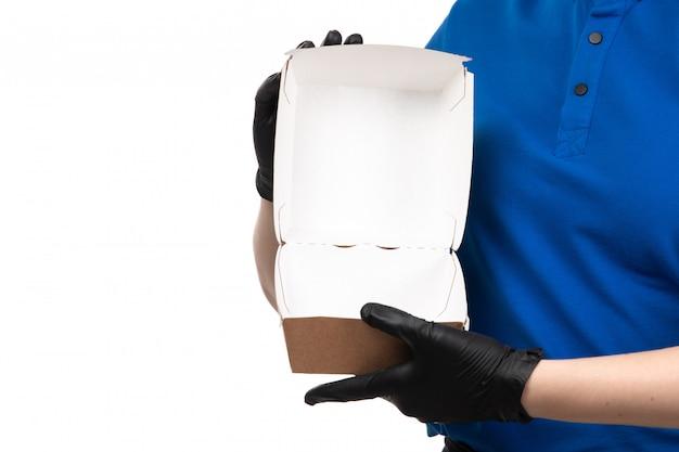 Widok Z Przodu Młoda Kobieta Kurier W Niebieskiej Jednolitej Czarnej Masce I Rękawiczkach Trzyma Pusty Pakiet Dostawy żywności Darmowe Zdjęcia
