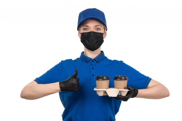 Widok Z Przodu Młoda Kobieta Kurier W Niebieskiej Jednolitej Czarnej Masce I Rękawiczkach Trzymających Filiżanki Kawy Darmowe Zdjęcia