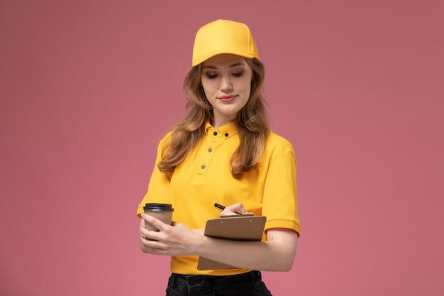 Widok Z Przodu Młoda Kobieta Kurier W żółtym Mundurze, Trzymając Filiżankę Kawy Zapisując Notatki Na Ciemnoróżowym Biurku Jednolity Pracownik Usługi Dostawy Darmowe Zdjęcia