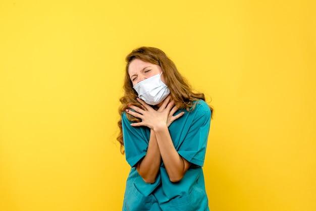 Widok Z Przodu Młoda Kobieta Lekarz Mający Problemy Z Oddychaniem Na żółtej Przestrzeni Darmowe Zdjęcia