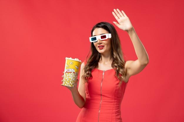 Widok Z Przodu Młoda Kobieta Trzyma Pakiet Popcornu D Okulary Na Czerwonej Powierzchni Darmowe Zdjęcia