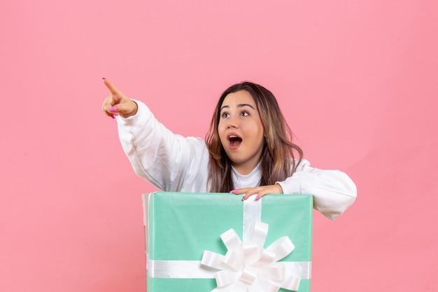 Widok Z Przodu Młoda Kobieta Ukrywa Się W środku Obecnego Na Różowej Podłodze Model Kobiet Zdjęcie Kolor świątecznej Piżamy Party Darmowe Zdjęcia
