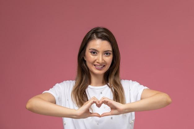 Widok Z Przodu Młoda Kobieta W Białej Koszuli Uśmiechnięta Pokazując Znak Serca Na Różowej ścianie, Kolor Kobiety Stanowią Model Darmowe Zdjęcia