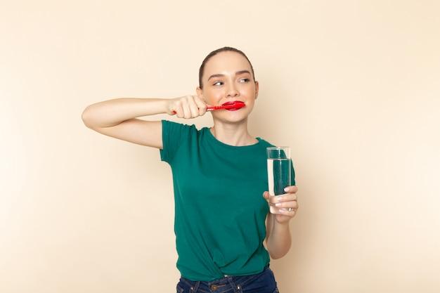 Widok Z Przodu Młoda Kobieta W Ciemnozielonej Koszuli I Niebieskich Dżinsach, Czyści Zęby Na Beżu Darmowe Zdjęcia