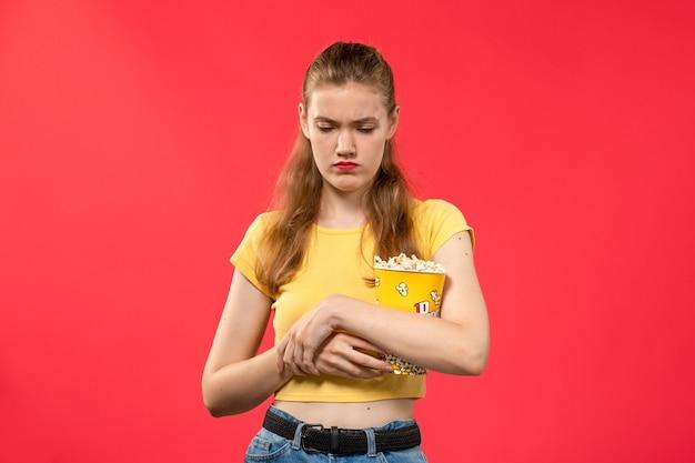 Widok Z Przodu Młoda Kobieta W Kinie Trzymając Pakiet Popcornu I Podkreślił Na Czerwoną ścianę Filmy Teatr Kino Przekąskę Zabawny Film Darmowe Zdjęcia