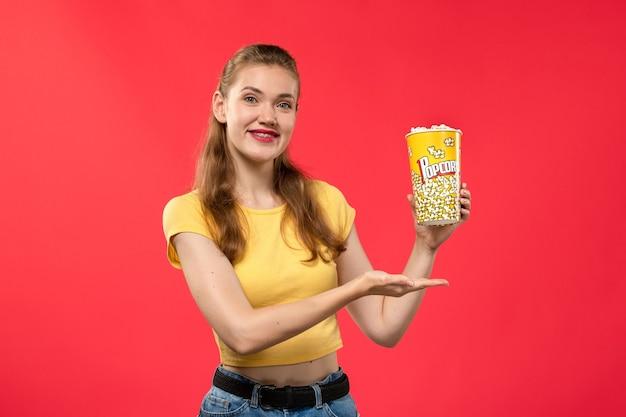 Widok Z Przodu Młoda Kobieta W Kinie Trzymając Pakiet Popcornu Z Lekkim Uśmiechem Na Czerwonej ścianie Filmy Teatralne Kino Kobiece Film Zabawa Darmowe Zdjęcia