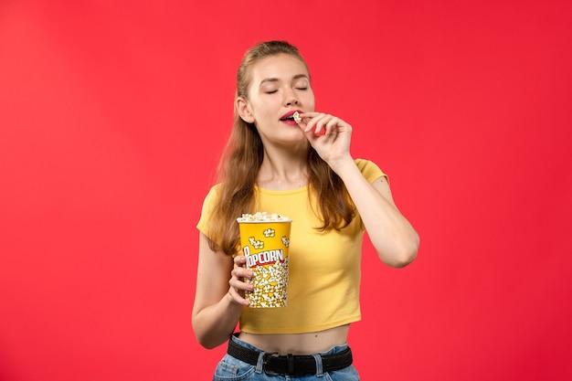 Widok Z Przodu Młoda Kobieta W Kinie Trzymając Popcorn I Jedzenie Na Czerwonej ścianie Filmy Dziewczyna Kino Teatralne Darmowe Zdjęcia