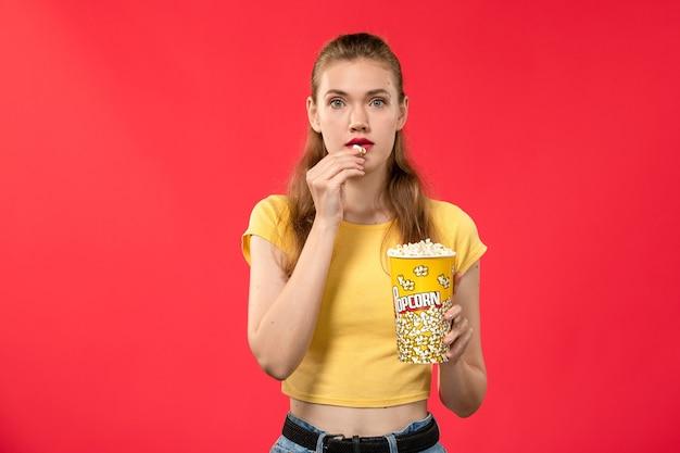 Widok Z Przodu Młoda Kobieta W Kinie Trzymając Popcorn I Jedzenie Na Czerwonej ścianie Filmy Teatralne Kino Kobiece Zabawa Film Darmowe Zdjęcia