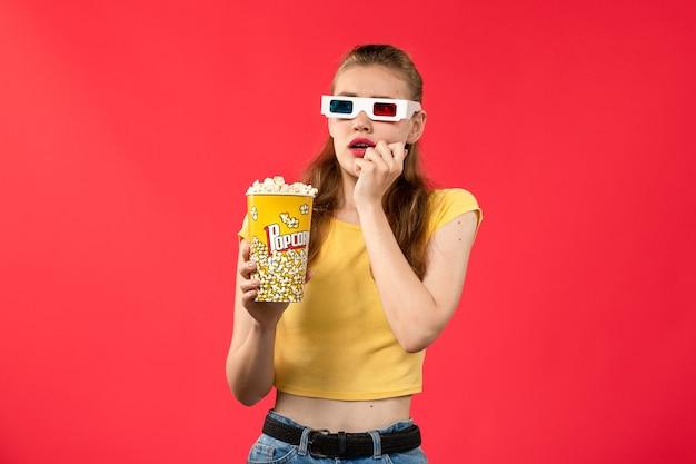 Widok Z Przodu Młoda Kobieta W Kinie Trzymając Popcorn Na Czerwonej ścianie Filmy Teatr Kino Przekąska Kobieta Film Zabawa Darmowe Zdjęcia