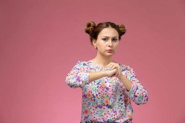 Widok Z Przodu Młoda Kobieta W Koszuli W Kwiaty I Niebieskich Dżinsach Z Zaciśniętą Pięścią Pozuje Na Różowym Biurku Darmowe Zdjęcia