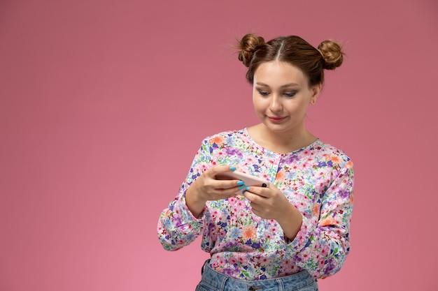 Widok Z Przodu Młoda Kobieta W Koszuli Zaprojektowanej W Kwiatki I Niebieskie Dżinsy Grając W Gry Przez Telefon Na Różowym Tle Darmowe Zdjęcia