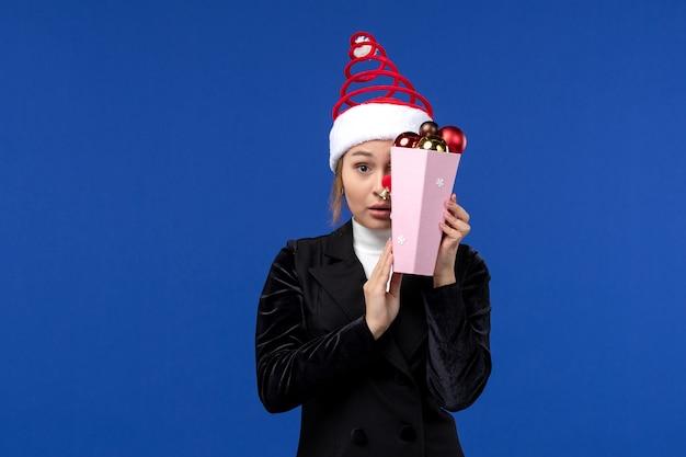 Widok Z Przodu Młoda Kobieta Zakrywająca Twarz Zabawkami Na Niebieskiej ścianie Emocja Nowy Rok Wakacje Darmowe Zdjęcia