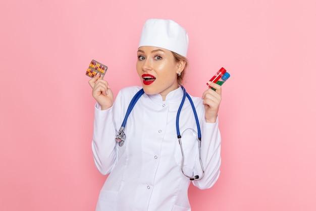 Widok Z Przodu Młoda Lekarka W Białym Garniturze Medycznym Z Niebieskim Stetoskopem Trzymająca Pigułki I Kolby Na Różowym Szpitalu Medycznym Medycyny Kosmicznej Darmowe Zdjęcia