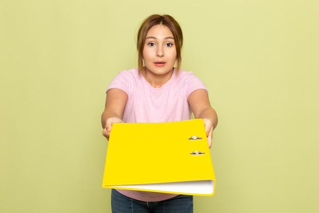 Widok Z Przodu Młoda Piękna Dziewczyna W Niebieskich Dżinsach Różowy T-shirt Pozowanie I Rozdaje żółty Plik Na Zielono Darmowe Zdjęcia